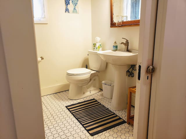 The tile, pedestal sink, and repurposed door from Habitat for Humanity's ReStore add a little vintage charm to the bathroom.