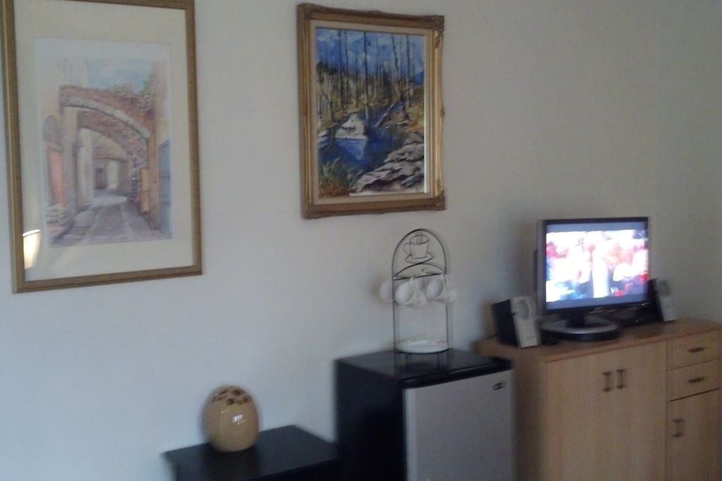 In room TV, refrigerator, and pleasant wall  treatment.