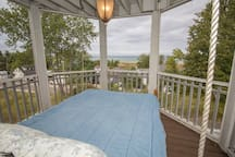 Screened in patio bed swing overlooking the lake