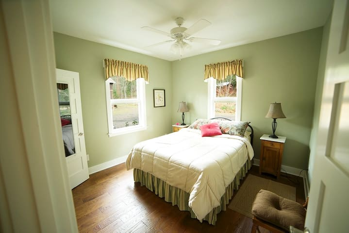 Downstairs corner bedroom with queen bed next to full bath.