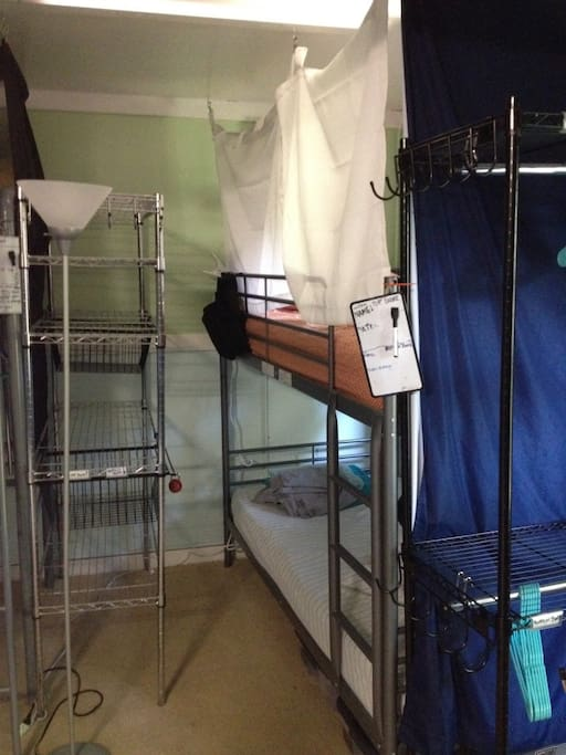 View of another top bunk in room. Storage shelves for guests in bunk beds shown as well