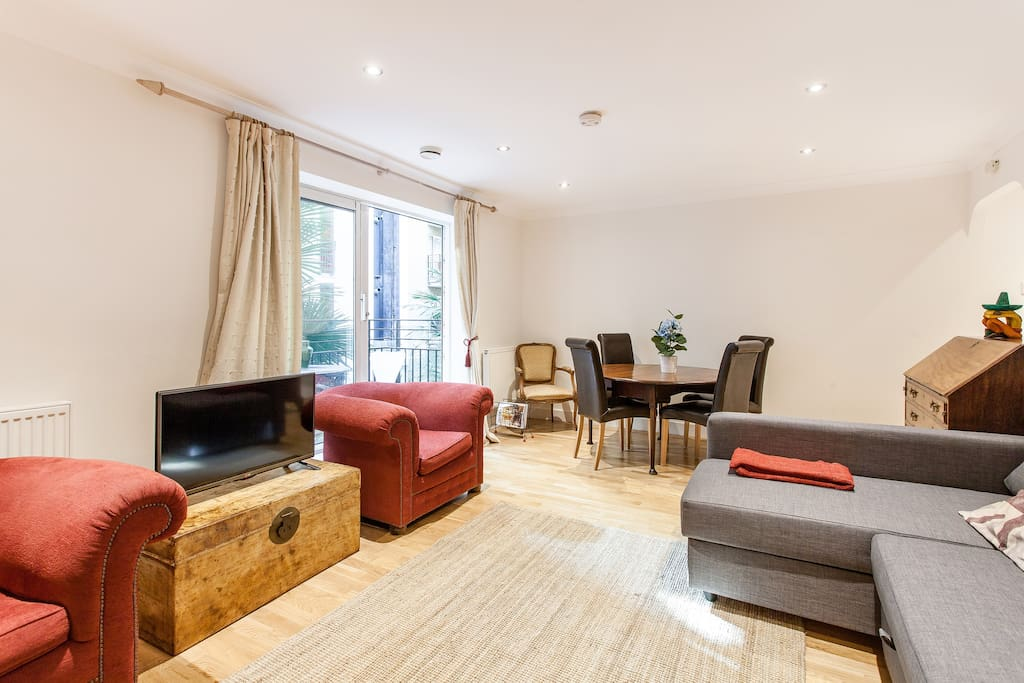 Beautiful spacious living room decorated to a high standard with dining table, LED TV