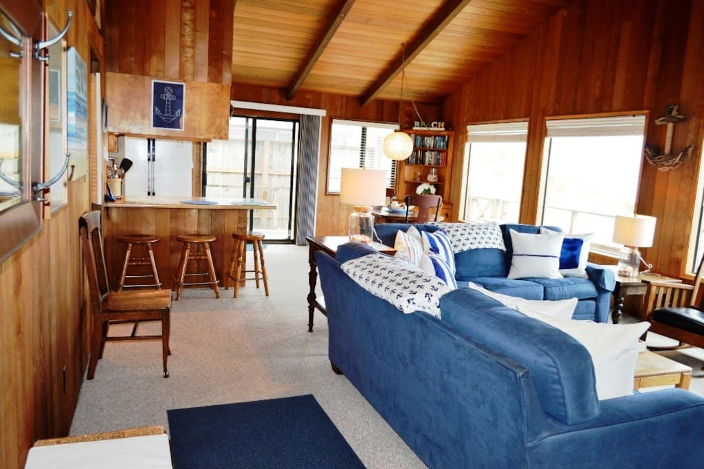 Living room with a flat screen satellite TV/DVD player, wood burning fireplace, two couches and spectacular ocean views