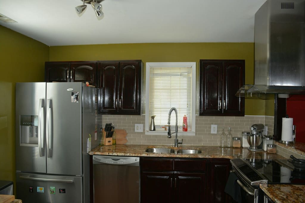 Renovated kitchen with granite countertops, new stainless steel appliances including an induction stovetop.