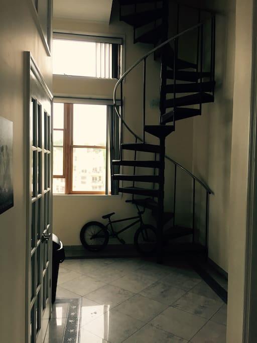 Walking through front door of apt. Bedroom is up spiral staircase
