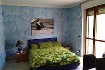 Ampia e accogliente camera da letto che si affaccia sul balcone posteriore con vista su orto e colline