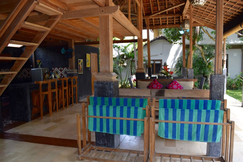 The open-air Javanese timber building, called a joglo, serves as our outdoor living space. Complete with dining, lounge, kitchen/bar and a third bathroom. Upstairs is a massage area with 2 massage tables where on-call therapists can do their magic .
