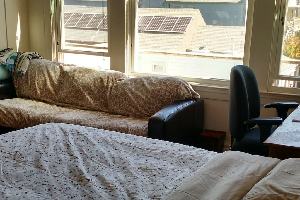 The room has a queen-size bed, large desk, and a couch, with large, bright windows looking out over the garden.