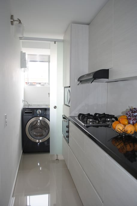 portion of kitchen. oven, microwave, stove. washing/drying machine