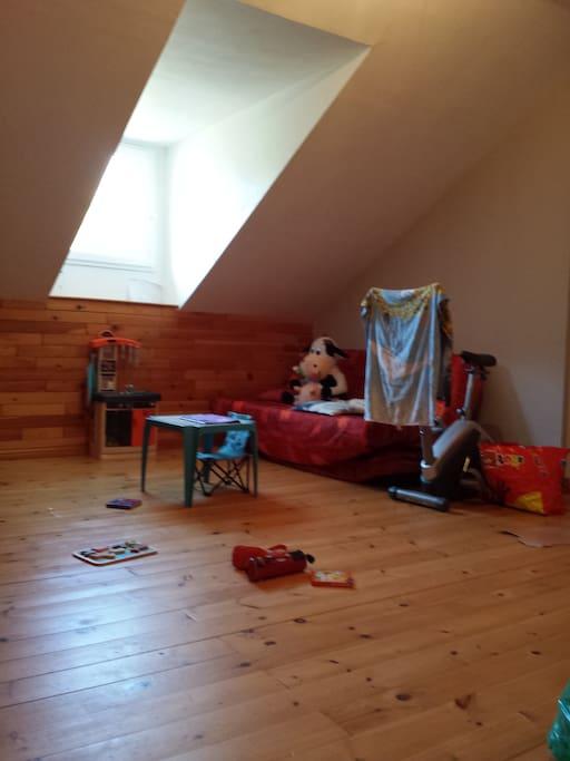 Espace détente de 20m² avec canapé et jeux de société (pour enfant essentiellement).