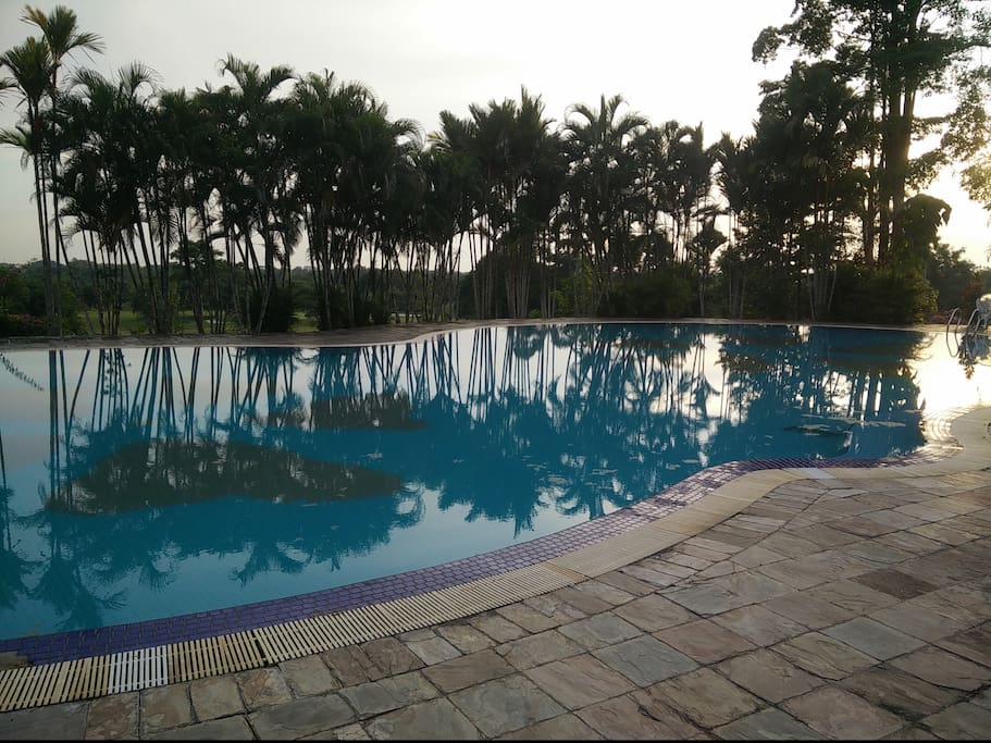 large swimming pool in front of the hotel with a great view of the golf coarse