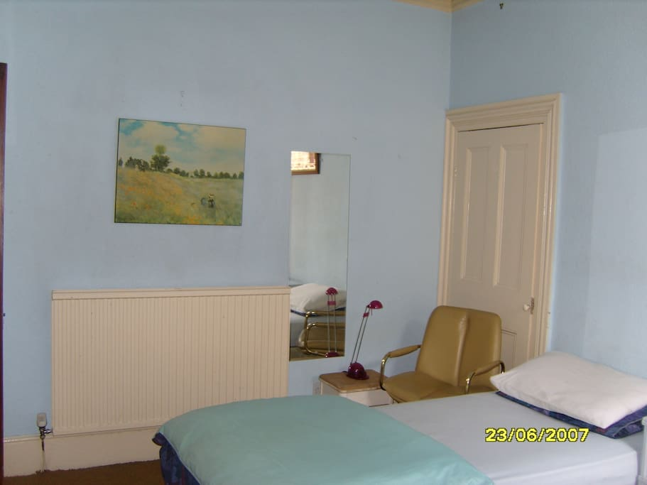 Room with small double bed (4 foot) and single bed overlooking parkland.