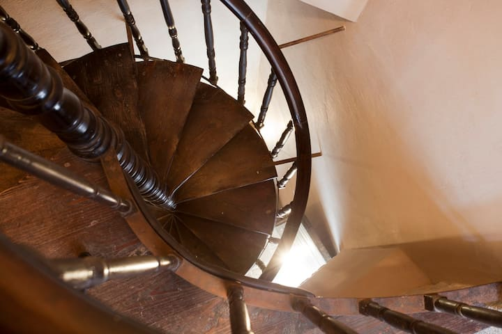 A narrow spiral staircase gives access to the apartment