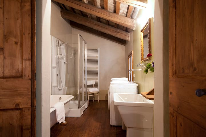 Spacious bathroom with shower-tub and washing machine