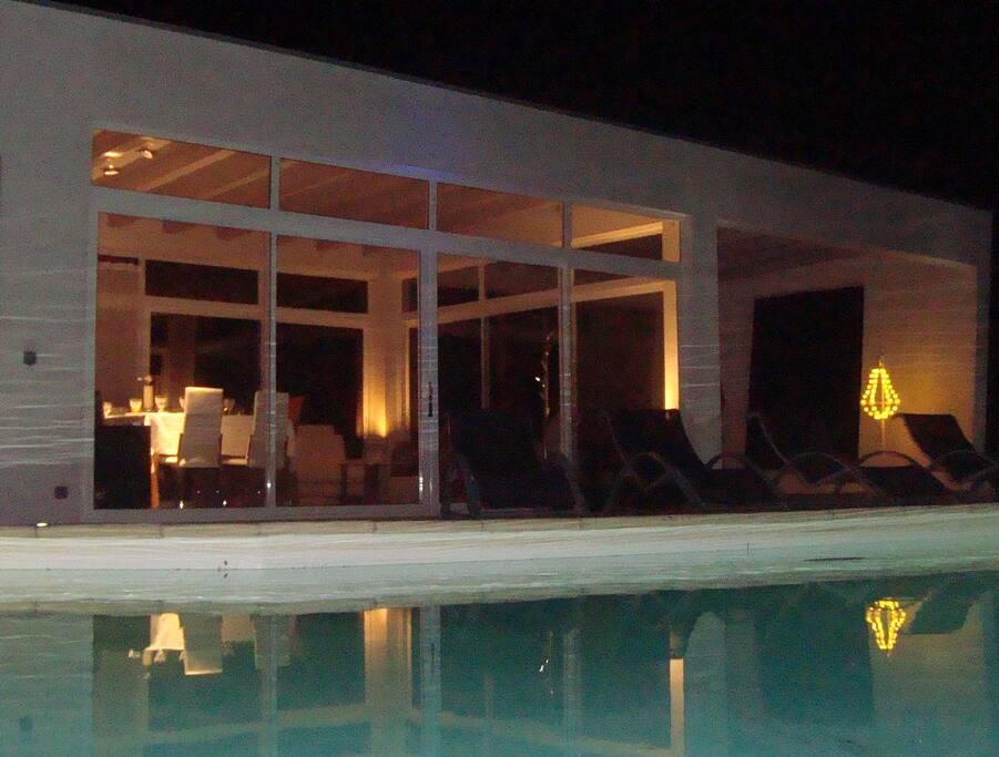 Le poolhouse avec sa terrasse couverte et ses canapés Stark
