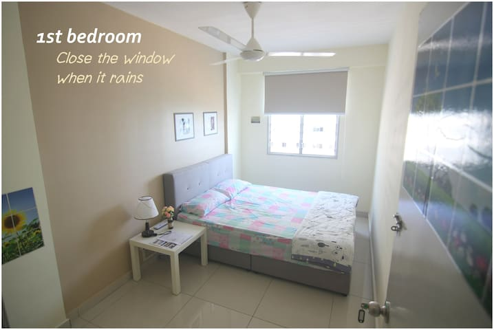 [1st bedroom] Queen-size bed, ceiling fan, clothes hanger & blind.