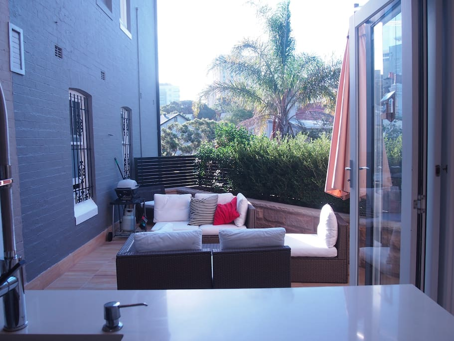 North facing outdoor space - sun all day and a big built-in umbrella if you need it.  Includes use of BBQ.