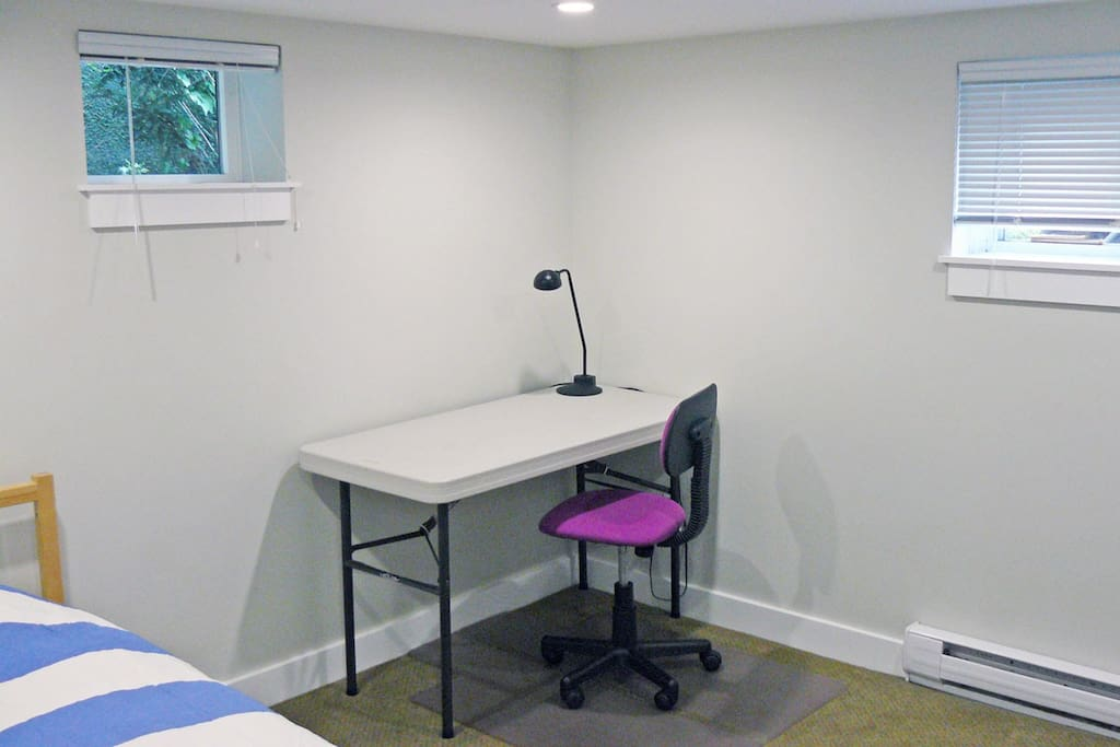 Room is supplied with desk, light and chair.