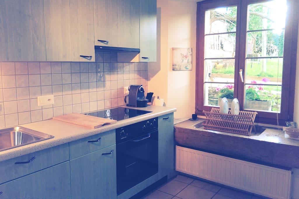 Cuisine agencée avec lave-vaisselle et machine à café (système Nespresso), vue sur les pâturages des Franches-Montagnes.