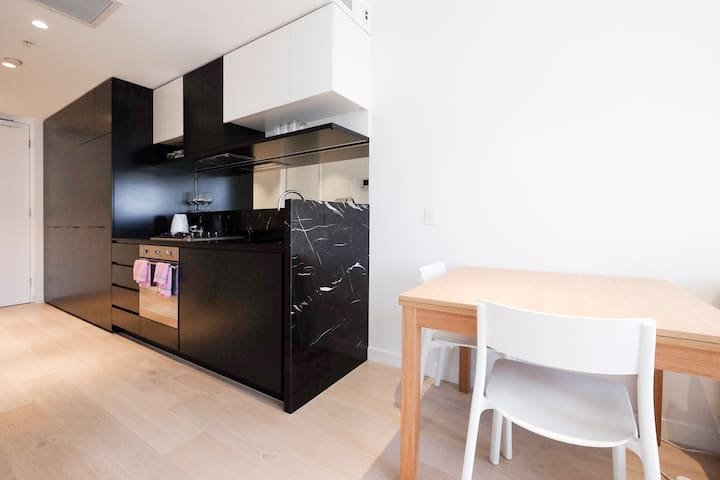 Kitchen and dining area, equipped with modern appliances, cooking and dining utensils.