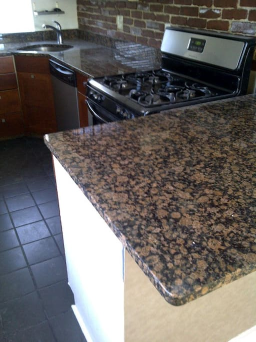 Granite counters, tile, and Cherry refaced cabinets.