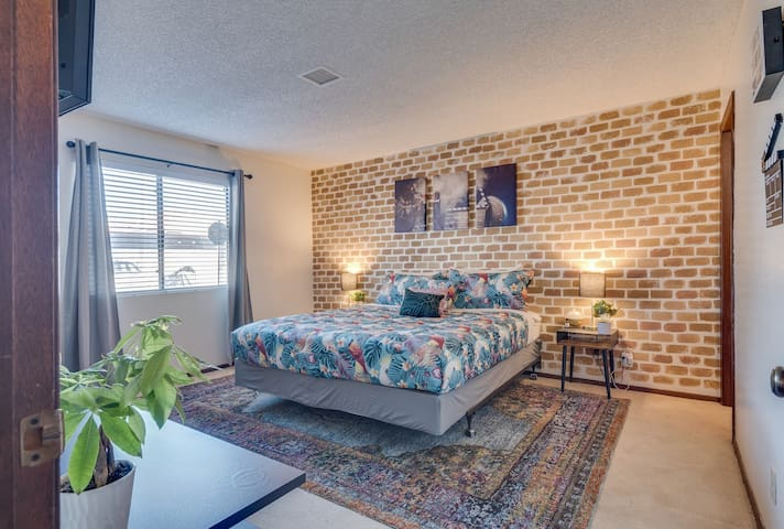 Beautiful Industrial design master bedroom with hand painted accent brick wall.