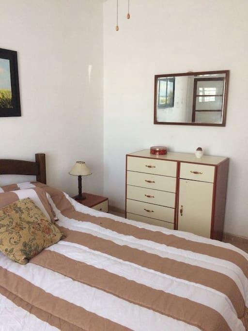 Dormitorio al frente con cama matrimonial, ventilador de techo y aberturas con rejas y postigo es de madera.