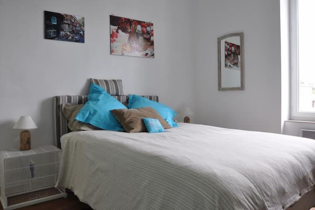 la chambre bleue, une des tables de nuit est une cage avec une oiseau en céramique.