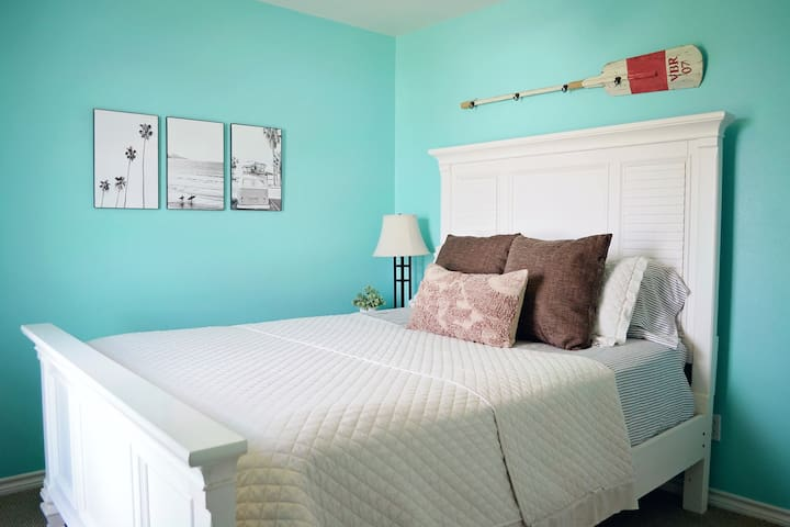 Bedroom #2 is located downstairs and has a queen sized bed, TV and modern coastal decorations.