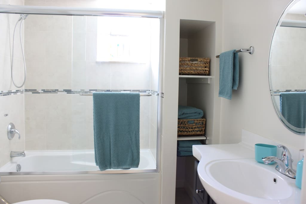 Clean bathroom with essentials such as towels, toilet paper, shampoo, conditioner, and body wash.