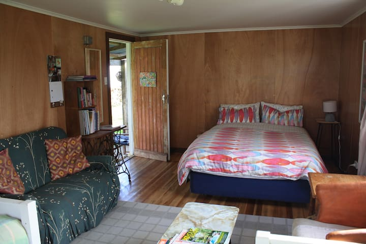 Door opening into guest room and double bed opposite two single beds