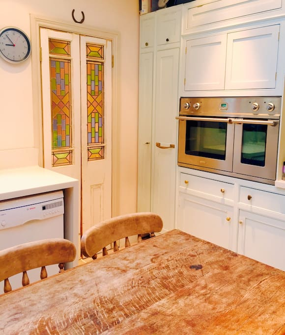 The dining area in the kitchen has a large table and can seat 8 people. There is a double electric oven and induction hob. The stained glass doors take you through to a utility room with washing machine and WC.