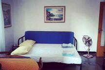 Divano letto in salotto, che diventa un comodo letto matrimoniale. Il soggiorno è dotato di una televisione, un ventilatore e un tavolo con 4 sedie per pranzare e cenare.