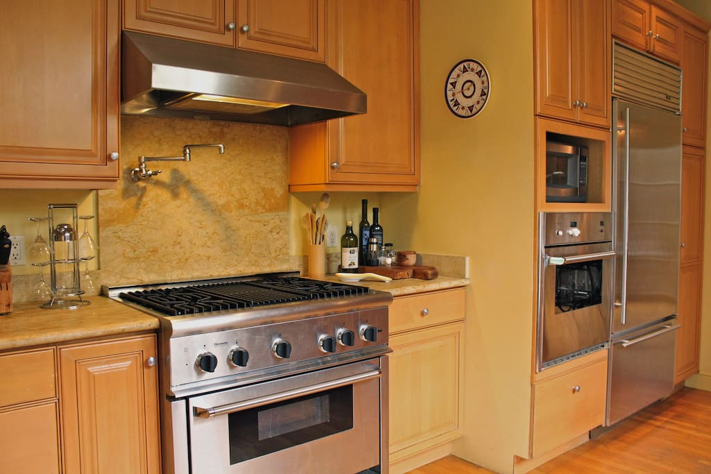 Kitchen, includes four range gas stove, microwave, dishwasher, oven, and utensils.