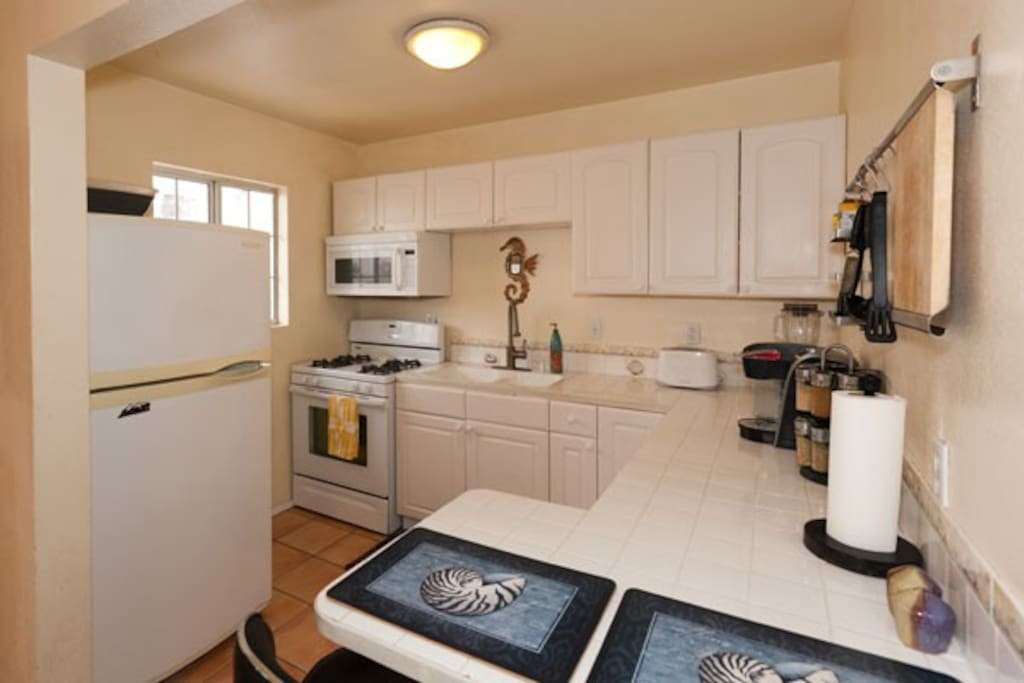 full kitchen with gas range blender, toaster coffee maker, eating area.