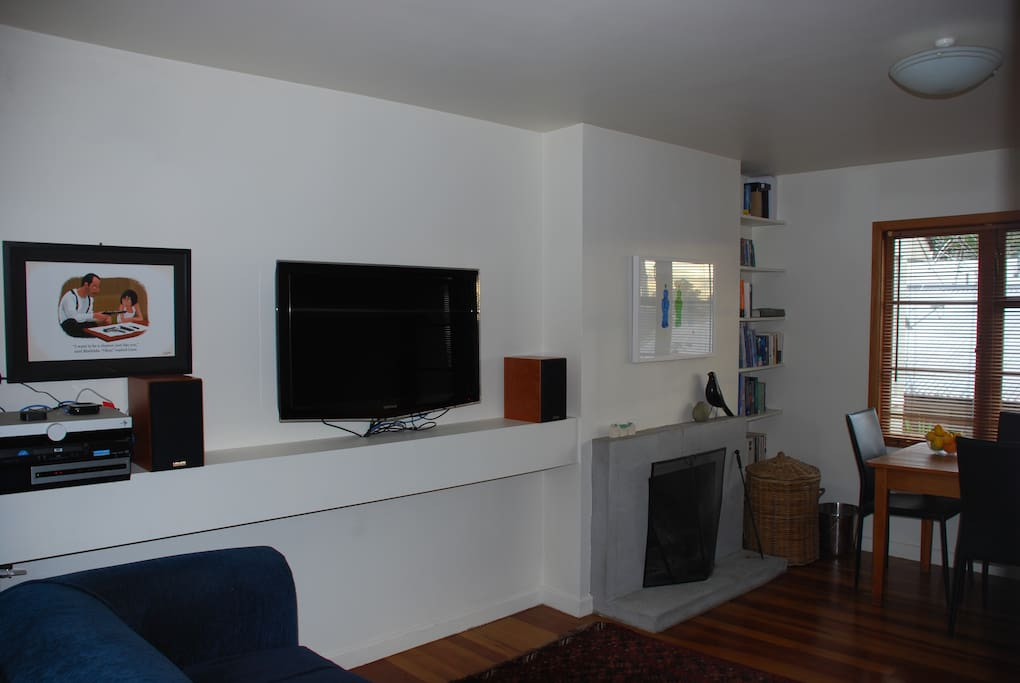 Wall hung tv with Tivo, small stereo, dining table and 4 chairs.
