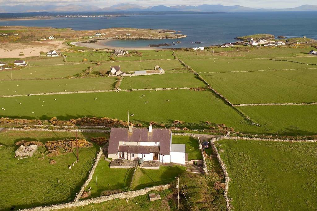 The view from the front of the house with Rhoscolyn Bay in the foreground and Snowdonia in the distance.
