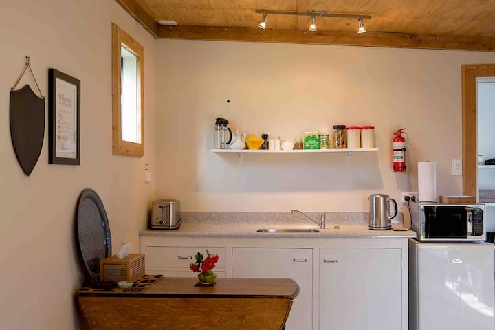 The kitchenette has a refrigerator, microwave, electric jug and toaster.  Crockery and cutlery supplied. Please note: There are no elements or oven.  Wi-fi instructions are on the welcome card in the room.  Easy to fold out table.
