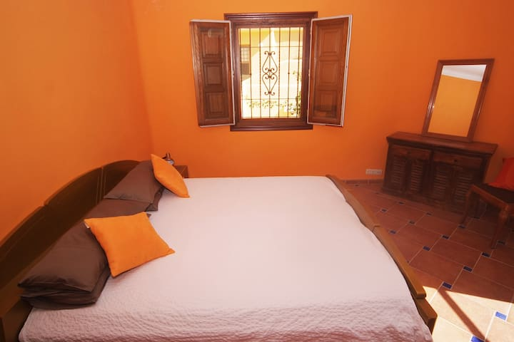 Bedroom 2 with a king sized bed, large wardrobe, dressing table and access to a balcony