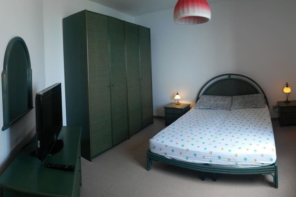 Das Schlafzimmer mit Fernseher und Fenster zum Meer