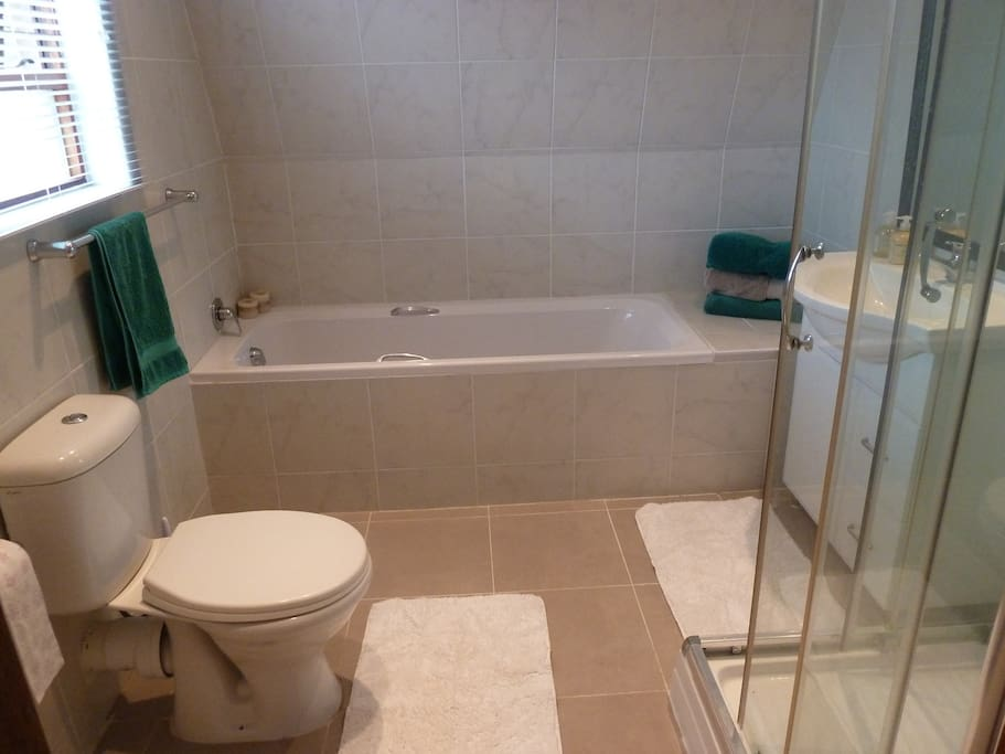 Large bathroom with soft bath towels, shower gel, shampoo and conditioner.