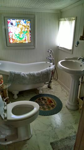 Bathroom with tub and free standing shower and mermaid stainded glass window