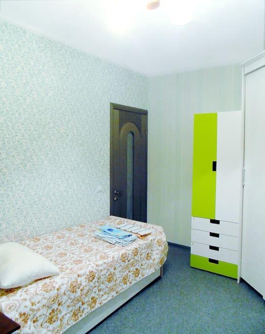 Кровать размером 200х80, шкаф с ящиками и штангой, справа большой белый шкаф-купе. Дверь в комнате запирается изнутри, а также закрывается на ключ снаружи