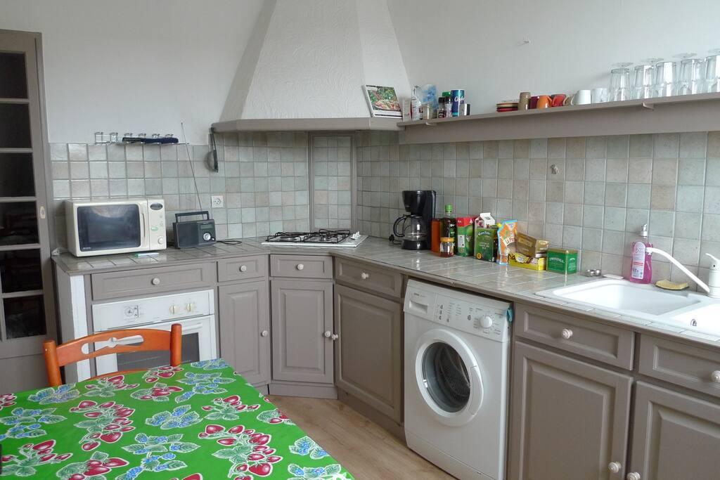 cuisine aménagée avec base de produits pour cuisiner, lave linge et lave vaisselle