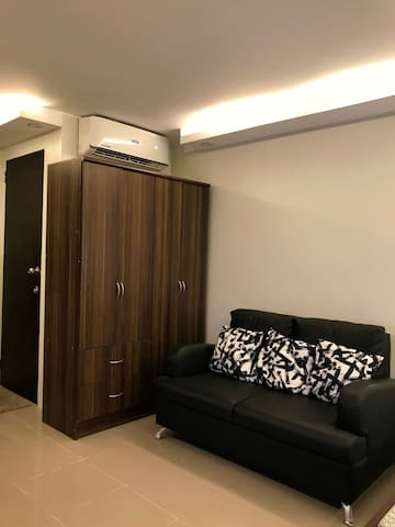 A comfortable sofa in front of the TV. The cabinet beside can be use for your folded clothes. A split type aircon is enough to cool the entire unit for comfort.