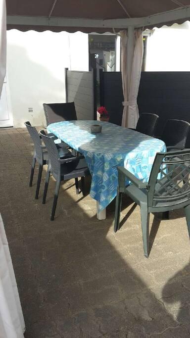Terrasse extérieure avec table sous tonnelle et BBQ