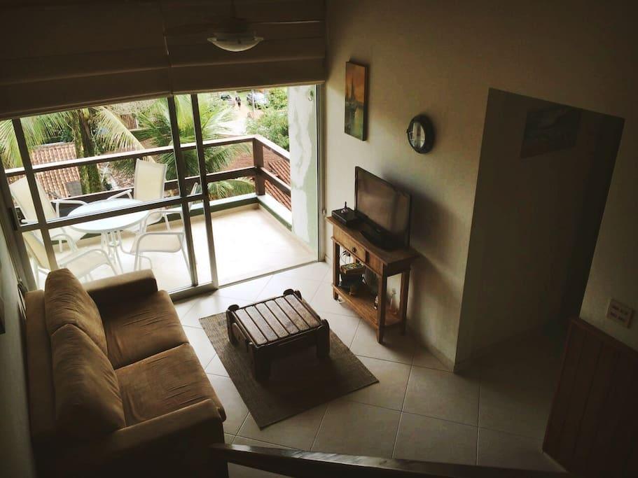 Sala com TV a cabo, varanda com mesa, espaço para rede e vista para mata