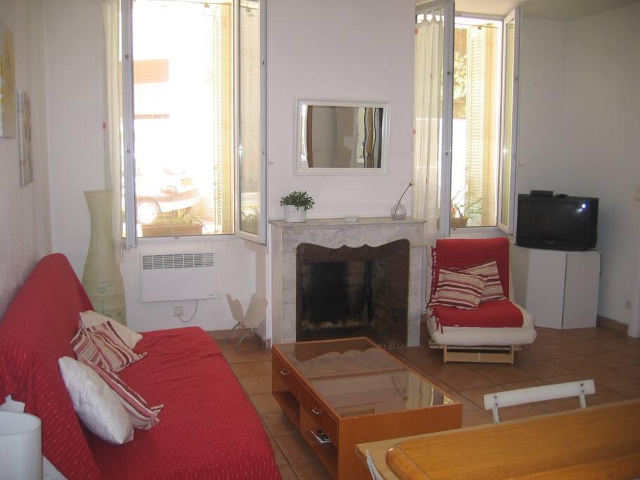 vaste pièce à vivre avec canapé clic-clac couchage quotidien et chauffeuse 1 place dépliable, tv avec tnt