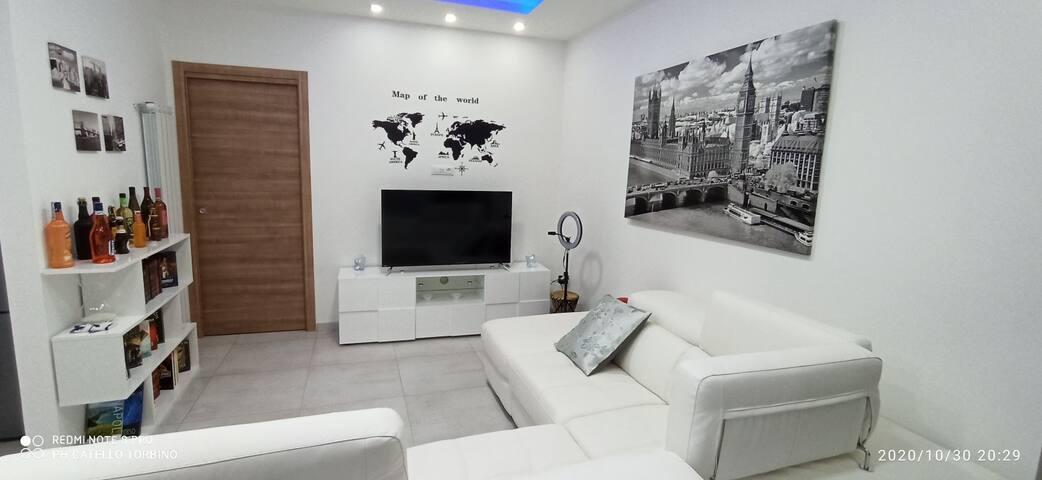 Ampio salotto con divano letto in pelle e cassetto porta oggetti. La Smart TV ha la connessione ad internet e l'abbonamento a Netflix incluso.