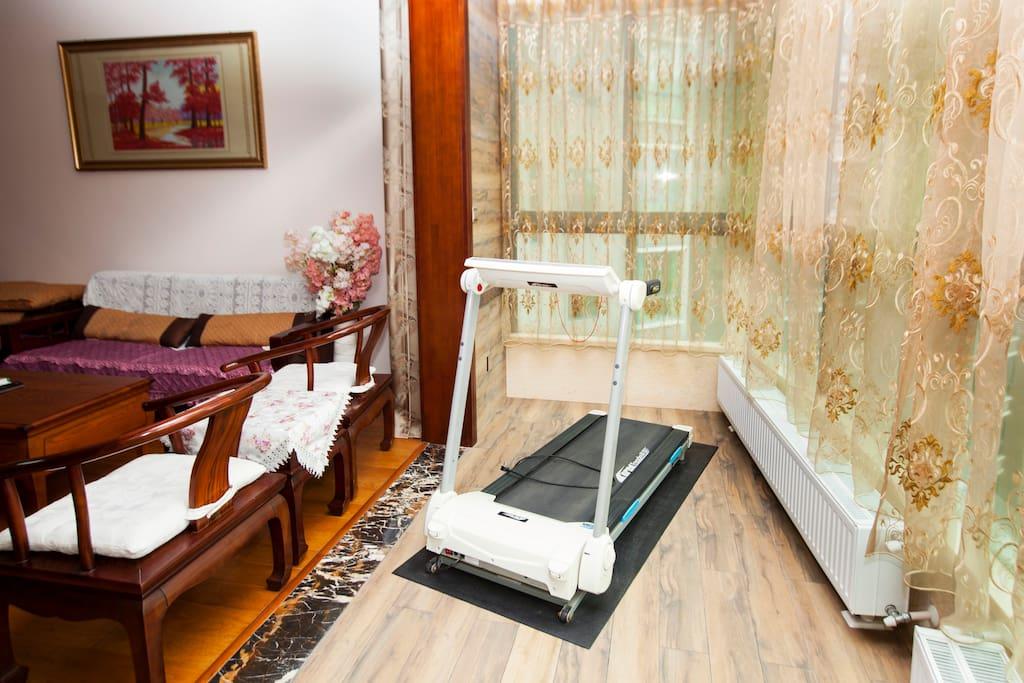 客厅阳台有一台跑步机,阳台窗户打开,可以一边呼吸清晨的清新空气一边健身。